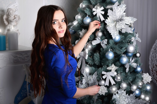 La ragazza in un vestito blu decora un albero di natale
