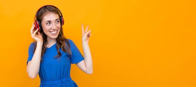 La ragazza in un vestito blu gode dei musicisti in cuffie su giallo con lo spazio della grande copia. concetto di pubblicità