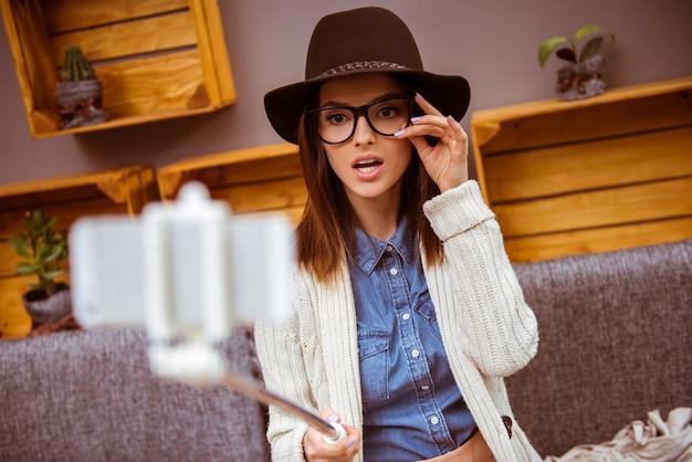 La ragazza in una caffetteria prende un selfie con gli occhiali.