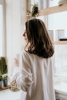 La ragazza in una camicia bianca beve il caffè di mattina in una cucina.