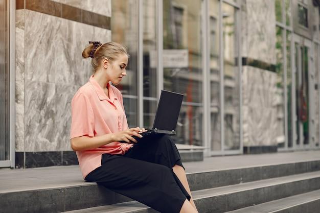 La ragazza in una camicia rosa che si siede vicino alla casa e usa il computer portatile