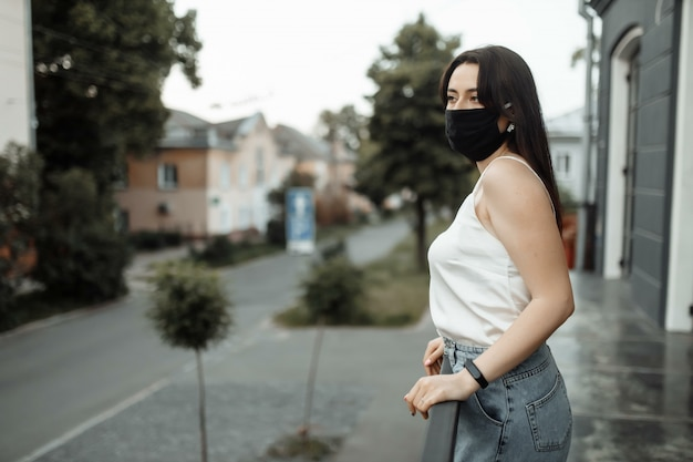 La ragazza in una maschera protettiva su un balcone guarda una città vuota
