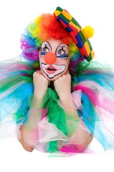 La ragazza in una tuta del clown isolato su uno sfondo bianco