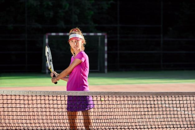 La ragazza in uniforme rosa gioca a tennis al campo da tennis all'aperto. concetto di sport.