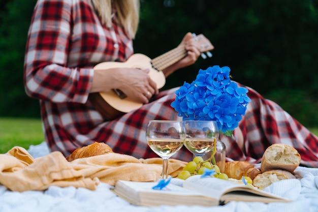 La ragazza in vestito a quadretti rosso e cappello che si siedono sulla coperta di picnic lavorata a maglia bianca gioca le ukulele e beve il vino. picnic estivo in giornata di sole con pane, frutta, bouquet di fiori di ortensia. messa a fuoco selettiva
