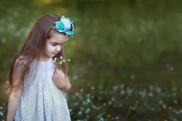 La ragazza in vestito bianco sta sentendo l'odore degli occhi dei fiori chiusi.