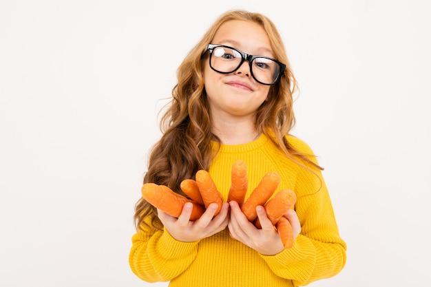 La ragazza in vetri tiene i frutti della carota su un fondo bianco isolato