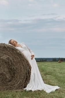 La ragazza incinta cammina in un campo vicino a covoni di fieno in un lungo abito bianco