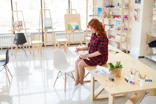 La ragazza incinta dipinge un'immagine della sua futura famiglia.