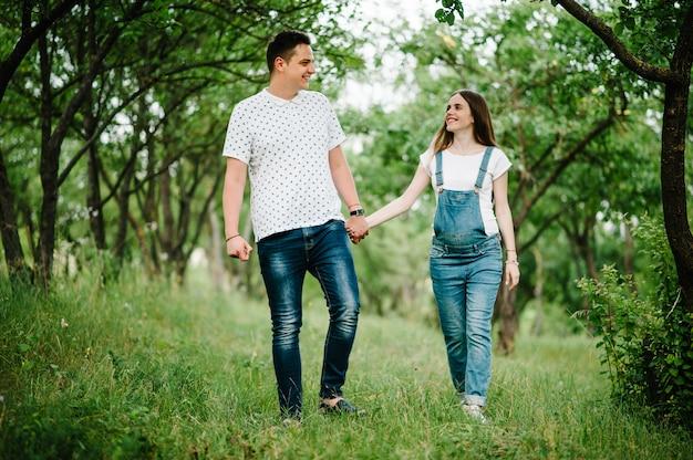 La ragazza incinta e il marito vanno all'aperto nel giardino con alberi.