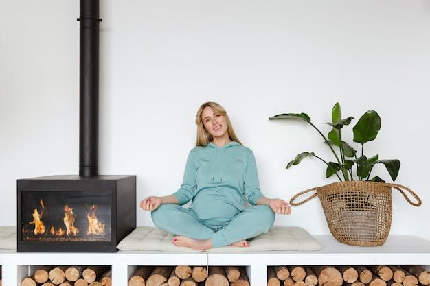 La ragazza incinta in abiti sportivi verdi si siede nella posizione di loto che fa yoga