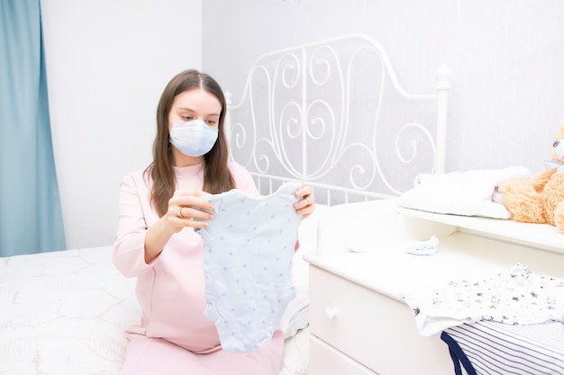 La ragazza incinta in una mascherina medica protettiva esamina le cose per un neonato. aspettativa di un bambino, maternità.