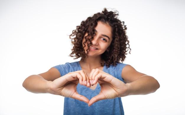 La ragazza indiana allegra mostra un cuore dalle sue mani. concetto di amore.