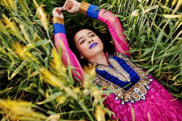La ragazza indiana tenera in saree, con le labbra viola compone posato al campo nel tramonto. modello alla moda dell'india.