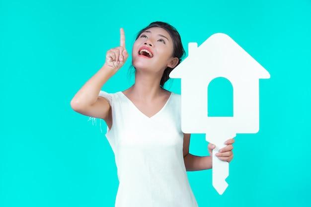 La ragazza indossava una camicia bianca a maniche lunghe con motivi floreali, tenendo in mano il simbolo della casa e mostrando vari gesti con un blu.