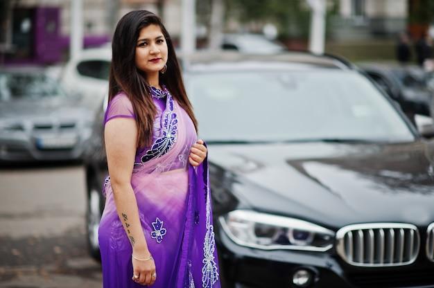 La ragazza indù indiana al saree viola tradizionale ha proposto alla via contro l'automobile nera del suv.