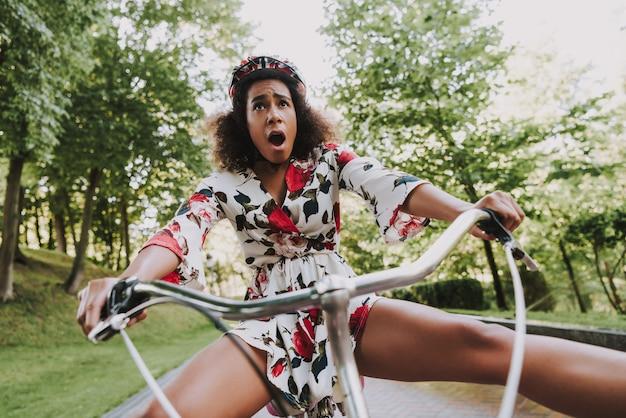 La ragazza latina spaventata sta ciclando nel parco.
