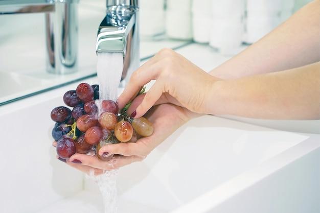 La ragazza lava l'uva sotto il rubinetto
