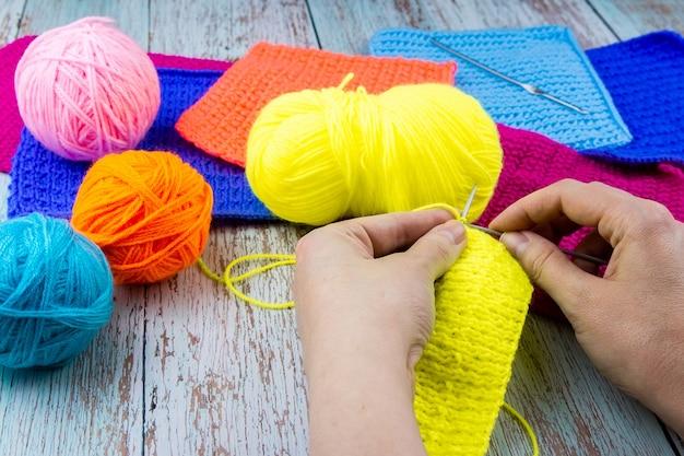 La ragazza lavora a maglia calza ferri da maglia