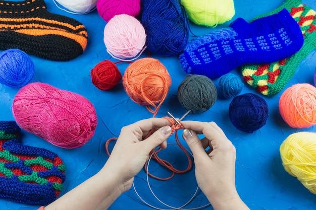 La ragazza lavora a maglia con ferri da calza
