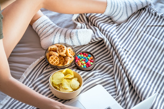 La ragazza lavora al computer in un letto e mangia fast food. cibo malsano: patatine, cracker, caramelle, waffle.