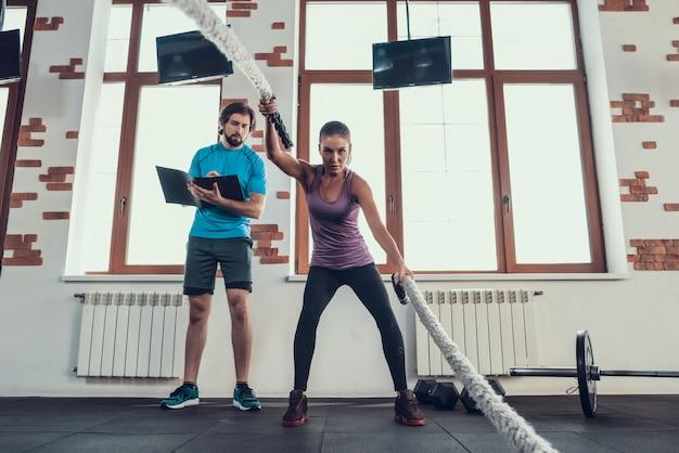 La ragazza lavora con le corde mentre l'allenatore prende appunti.