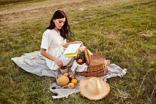 La ragazza legge un libro e mangia frutta all'aperto.
