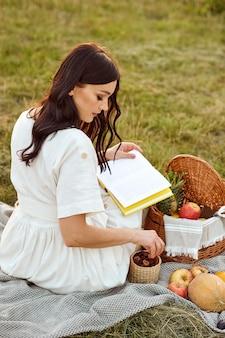 La ragazza legge un libro e mangia frutta e pastiglie all'aperto.