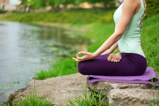 La ragazza magra del brunette fa sport ed esegue yoga belle e sofisticate in un parco estivo