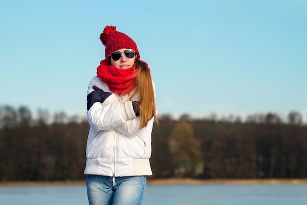 La ragazza magra rossa in occhiali da sole aviatore, berretto rosso, sciarpa rossa e giacca invernale bianca si congela in inverno
