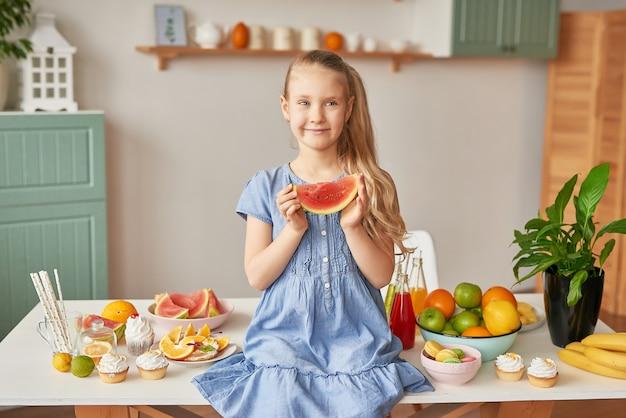 La ragazza mangia frutta in cucina