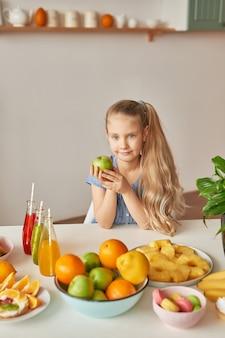 La ragazza mangia frutta su un tavolo pieno di cibo