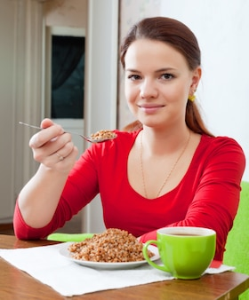 La ragazza mangia il grano saraceno con un cucchiaio
