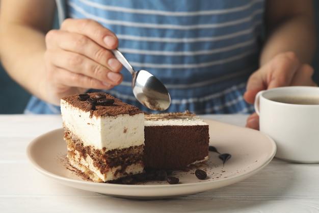 La ragazza mangia il tiramisù. composizione con deliziosa torta su fondo di legno bianco