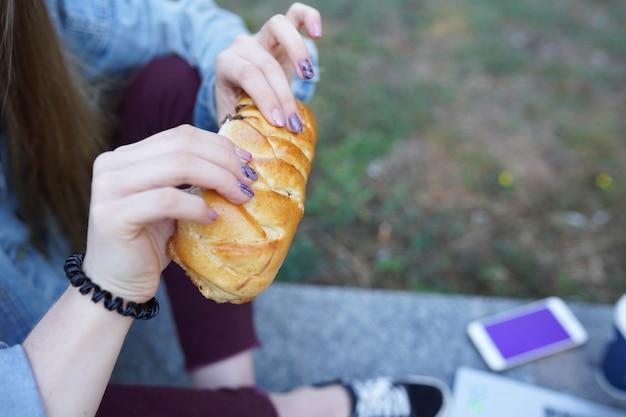 La ragazza mangia panino con cioccolato sulla strada