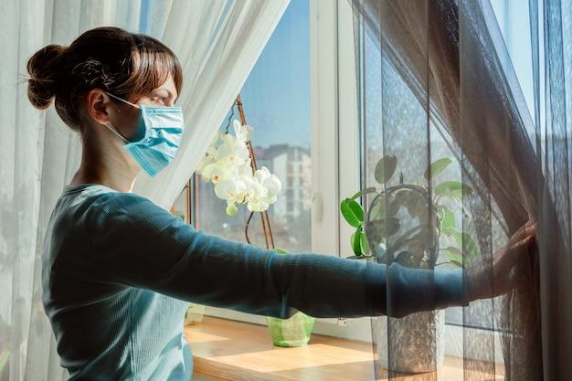 La ragazza mascherata guarda fuori dalla finestra. coronavirus e concetto di quarantena.