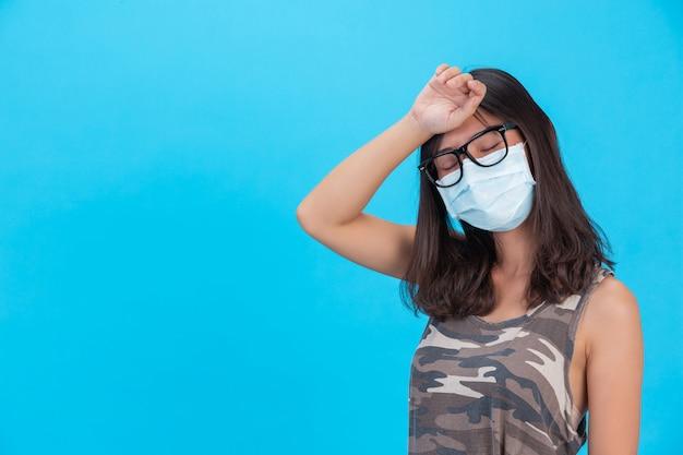 La ragazza mascherata mostra la sua mano con la fronte chiusa su una parete blu.
