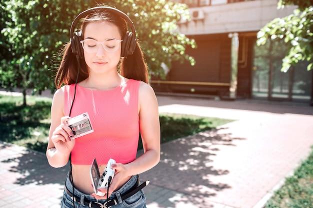 La ragazza melomania sta tenendo un cassete e lo sta guardando. ha aperto il giocatore tra le mani. la ragazza ha deciso di mettere cassete nel giocatore.