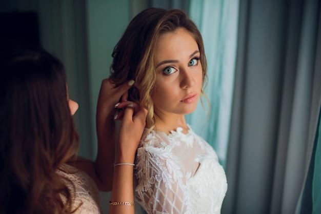 La ragazza mette su una sposa orecchino. giovane moglie ragazza in abito da sposa e con abiti da sposa