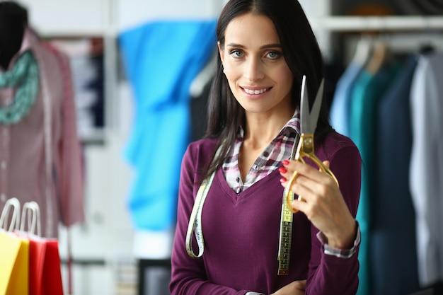 La ragazza mostra il suo dispositivo di lavoro, forbici per tessuto