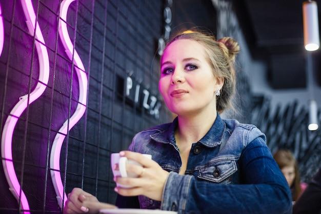 La ragazza nel caffè che beve caffè o tè, illuminazione al neon nel caffè