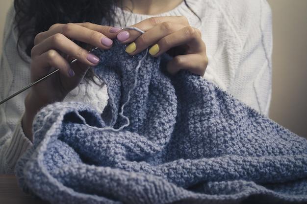 La ragazza nel maglione bianco tricotta il filo blu