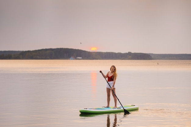 La ragazza nel mare si alza in piedi sulla tavola da sup paddle con bellissimi colori dell'acqua tramonto o alba.