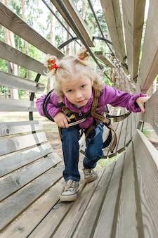 La ragazza nell'avventura che arrampica il parco dell'alto filo