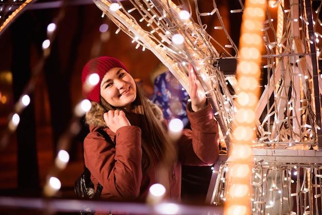 La ragazza nell'inverno copre il fondo delle luci, vicino alle luci dell'albero di natale