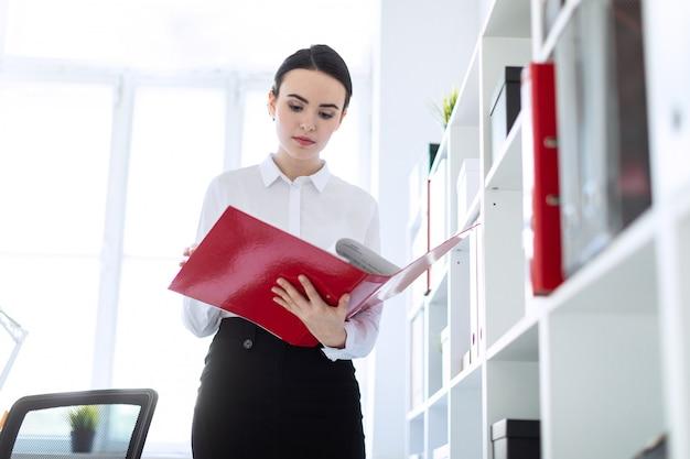 La ragazza nell'ufficio vicino allo scaffale e scorre la cartella con i documenti.