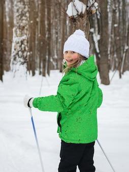 La ragazza nella foresta di sci invernale sta guardando indietro