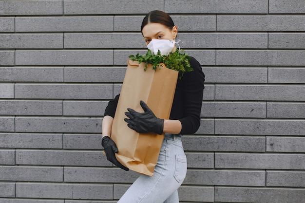 La ragazza nella maschera protettiva tiene il pacchetto con i prodotti