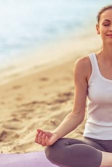La ragazza nello sport copre meditare e sorridere.