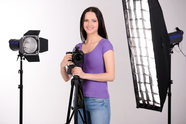 La ragazza nello studio fotografico lavora e sorride.